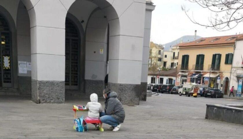 Scuole chiuse a Cava de' Tirreni, bambina con un banco davanti al Comune
